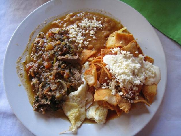 México – Café da manhã picante com nachos, chilaquiles, queijo, feijão e carne.