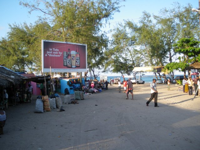 Na chegada à vila de Tofo, um outdoor ensina os gringos a pronunciar o nome da cerveja local em Português. Foto: Thaís Freitas