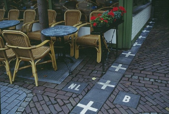 """Holanda e Bélgica - A fronteira da cidade de Baarle (dividida entre Holanda e Bélgica) é a fronteira mais confusa do mundo. Toda a cidade é cercada pela Holanda, mas possui 26 """"pedaços de cidade"""" pertencentes à Bélgica. Por isso existem marcações de fronteira, como a da foto, em todos os lugares para esclarecer as coisas."""